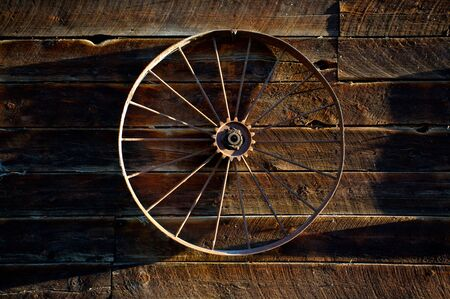farm implement: Antique farm machine wheel hanging on the side of old log barn Stock Photo