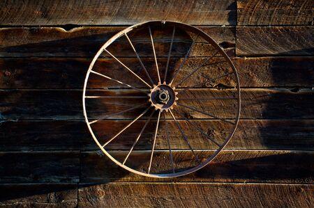 Antique farm machine wheel hanging on the side of old log barn Banco de Imagens