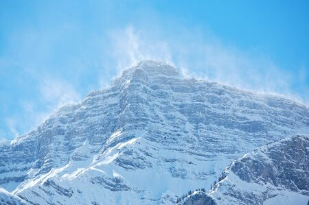 Snow blowing off top ridges of Mount Rundle in Banff National Park photo