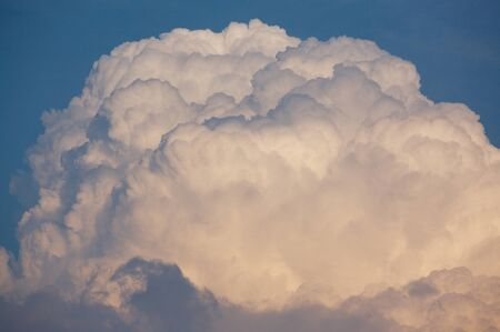 Huge cumulonimbus type thunder cloud forming in the evening sky. Stock Photo