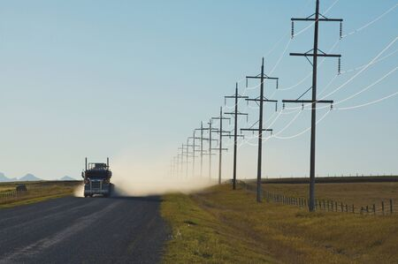 Truck on gravel road with power lines