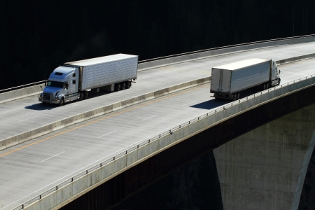 Semi-trailer trucks crossing a high level bridge in British Columbia Stock Photo