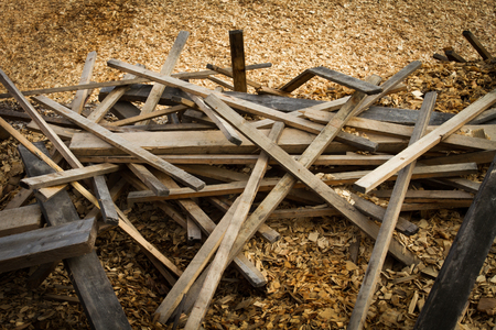 Pile of discarded lumber on plie of wood chips Stock Photo
