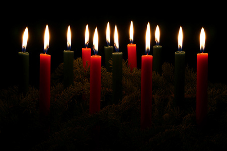 candle flame: Wide shot of red and green Christmas Candles and spruce tree boughs