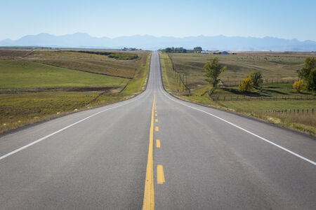 Open highway with the Canadian Rockies on the horizon near the town of High River, Alberta, Canada