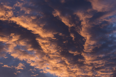 Brilliant orange colored clouds during a morning sunrise Stock Photo