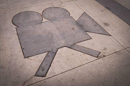 Grungy camera shape in a concrete sidewalk