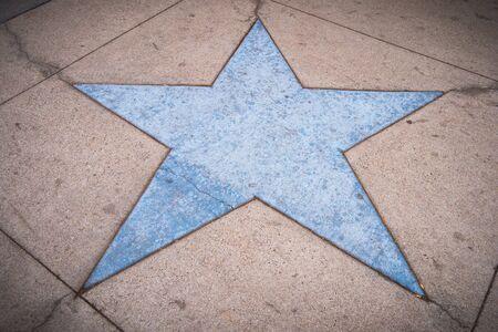 Blue star shape in a concrete sidewalk Foto de archivo