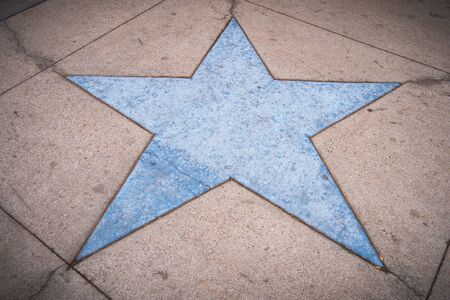 Blue star shape in a concrete sidewalk Stock Photo