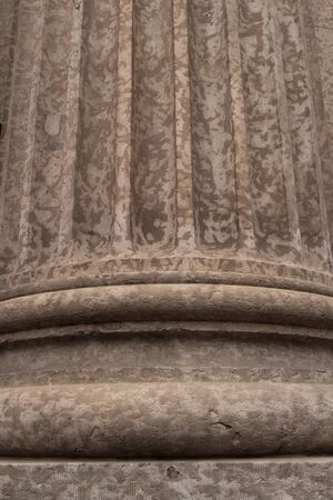 Close up architectural detail of the base of a Corinthian style stone pillar.