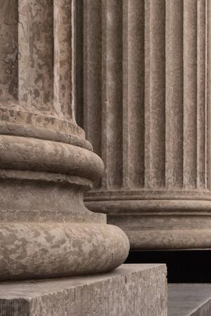 Close up architectural detail of the base of Corinthian style stone pillars.