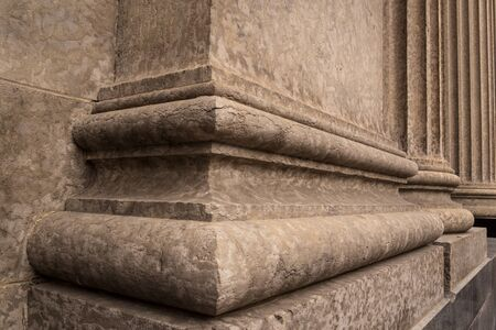 Close up architectural details of the base of Corinthian style stone pillars.