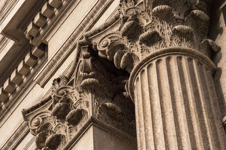 Close up architectural detail of the top of Corinthian style stone pillars.