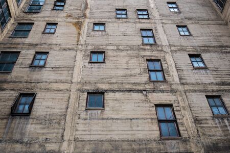 Grungy concrete wall with wood framed windows of an old city building Stock Photo