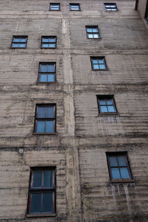 Grungy concrete wall with wood framed windows of an old city building Foto de archivo