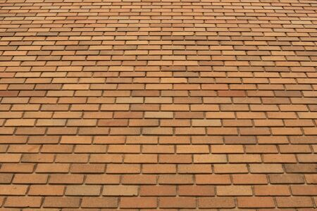 Low angle of large wall of smooth orange color bricks