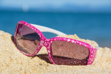 pink kids suglasses with a white floral design on the sand near the sea Stock Photo - 17628298
