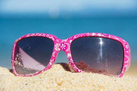 pink kids suglasses with a white floral design on the sand near the sea Stock Photo - 17628207