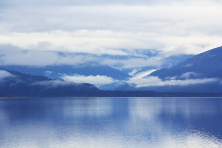 scenic mountain blue lake lanscape with the morning mist and clouds
