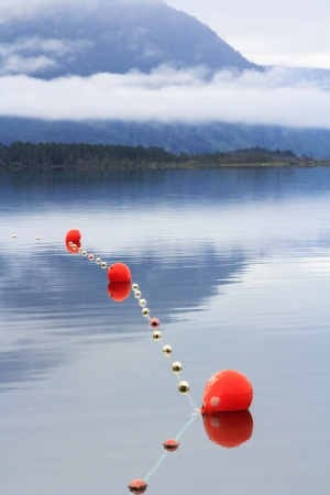 scenic mountain blue lake lanscape with the morning mist and clouds, fishing nets and orange floats Stock Photo - 17628168