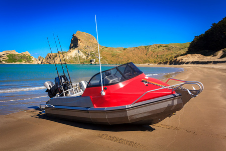 landscape with the red motor boat and the sandy beach, location - Castlepoint lighthouse, North Island, New Zealand