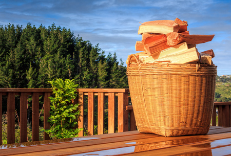 sunny landscape, basket with chopped firewood in the basket at the table - alternative energy, location - Wellington, North Island, New Zealand