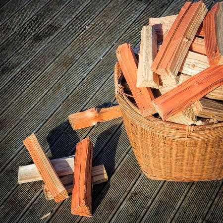 chopped firewood stack at the basket at the wooden floor photo Stock Photo