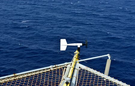 helideck: The wind velocity and direction indicator is set on the corner of oil rig helideck .