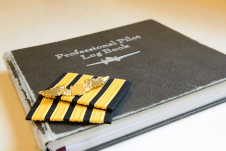 Four bar sign and golden metal wing of pilot put on the old pilot log book