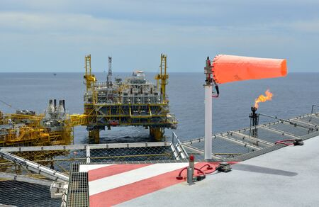 helideck: The wind sock is set on the oil rig to showing wind direction for  helicopter landing . Stock Photo