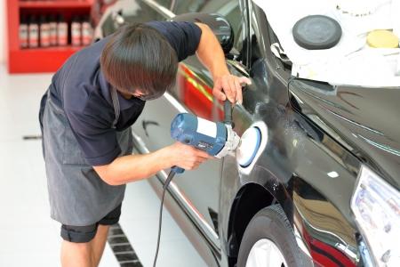The man is polishing the black car with polish machine.