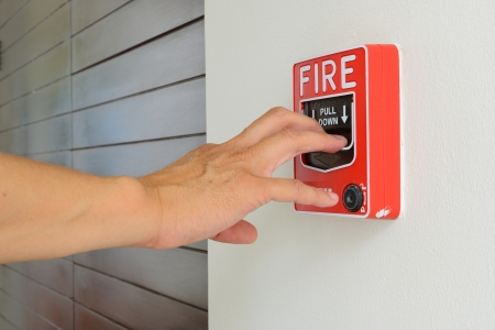 fire safety: The hand of man is pulling fire alarm on the wall next to the door Stock Photo