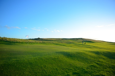 golf course: The golf player is  playing on the nice golf course fairway.