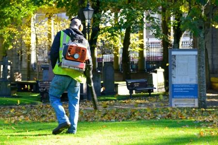 hojas secas: Operativo Landscaper gasolina soplador de hojas en el parque de la ciudad. Editorial