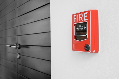 alarm button: color fire alarm switch on black and white wall Stock Photo