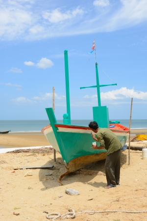 The senior man is painting side of fishing boat that on the beach in thailand. photo