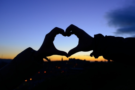 Silhouet van de handen in de vorm van hart, als geliefden hebben aangeraakt in het najaar met zonsondergang op stad achtergrond