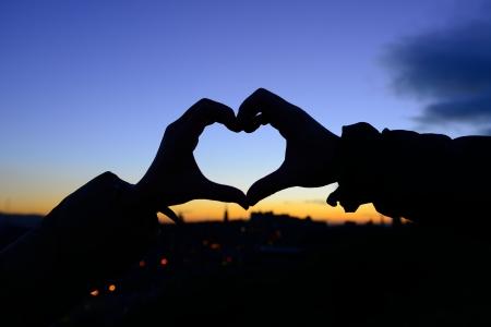 corazones azules: Silueta de las manos en forma de coraz�n cuando novios han tocado en oto�o con la puesta de sol en fondo de la ciudad