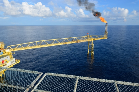 gas fire: The gas flare is on the oil rig platform.
