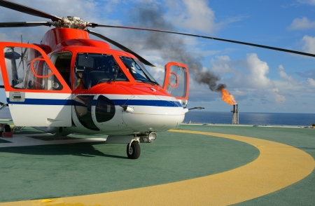 greenhouse gas: The helicopter park on oil rig to pick up worker with gas flare and blue sky backgroung