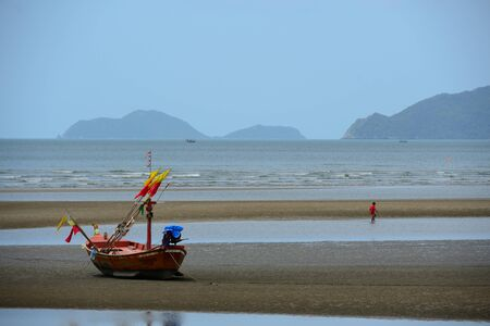 Wooden fishing boat  and boy is walking on beach photo