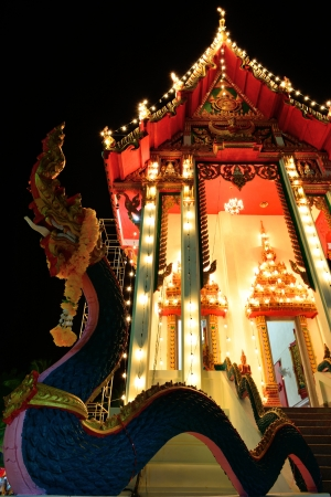 The exterior thai church is decorated with light at night