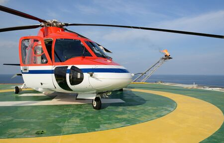 helideck: The helicopter park on oil rig to pick up worker with gas flare and blue sky backgroung