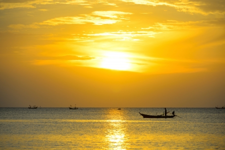 Fisherman are taking fishing boat to fish with sunrise backdrop. photo