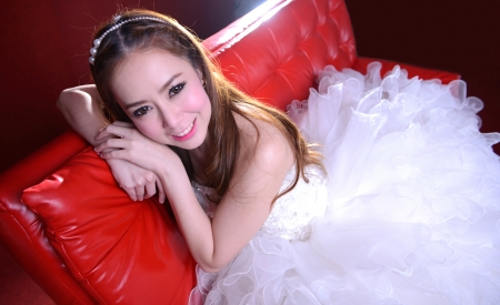 portrait of beautiful  smiling bride is on the red sofa photo