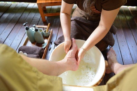 The women is washing his foot to prepare fot thai spa foot massage Standard-Bild