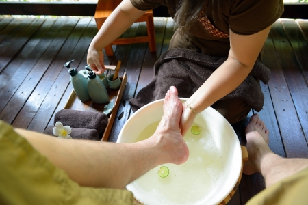 feet washing: The women is washing his foot to prepare for thai spa foot massage Stock Photo
