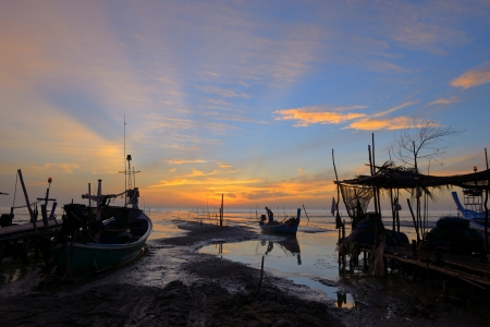 Fisherman is taking fishing boat to back home with sunrise background at thailand photo