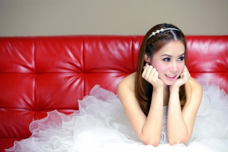 portrait of beautiful  smiling bride is on the red sofa