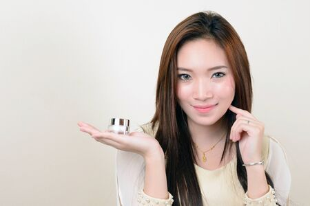 cosmetic beauty: portrait of beautiful  smiling healthy asian woman is holding cosmetic container